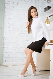 Une jeune femme brune séduisante vêtue d'un pull blanc et d'une jupe noire se penche au bord d'une table en ...