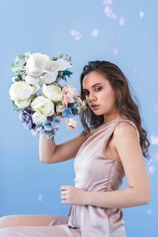 Jeune femme brune sensuelle avec une belle composition florale