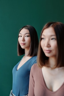 Jeune femme brune sérieuse d'origine asiatique aux cheveux longs vous regardant tout en se tenant derrière sa magnifique soeur jumelle en studio