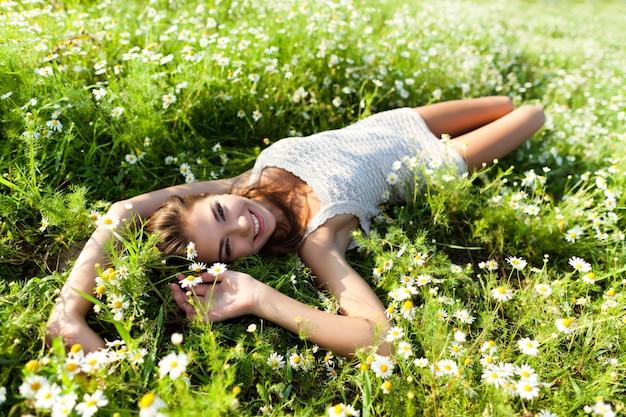 Jeune femme brune sexy allongée sur l'herbe et les fleurs et souriant le jour de l'été avec la nature verte et la rivière