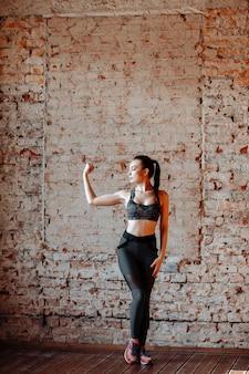 Jeune femme brune sexy en leggings de sport et haut posant contre un mur de briques dans le studio avec style loft.