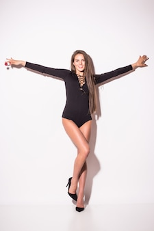 Jeune femme brune sexy en sous-vêtements noirs, isolé sur un mur blanc