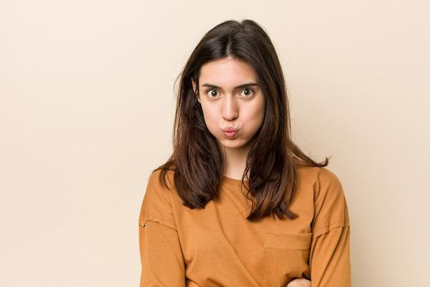 Jeune femme brune souffle les joues, a l'air fatigué