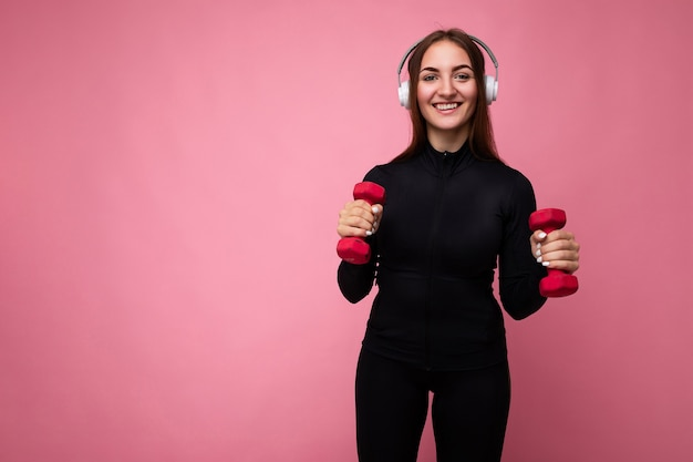 Jeune femme brune souriante assez positive portant des vêtements de sport noirs isolés sur rose