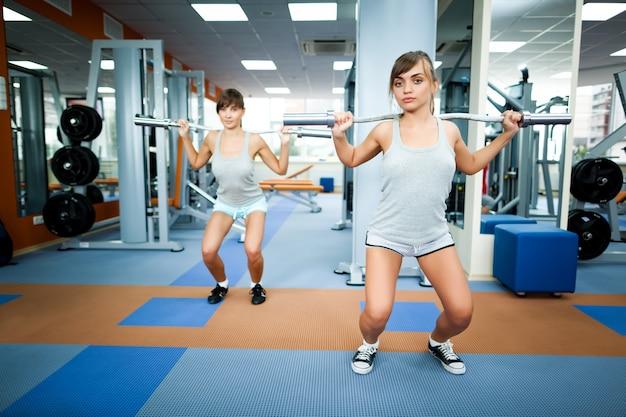 Jeune femme brune souriante instructeur en vêtements de sport gris montrant comment faire des squats d'haltères longs avec une autre fille