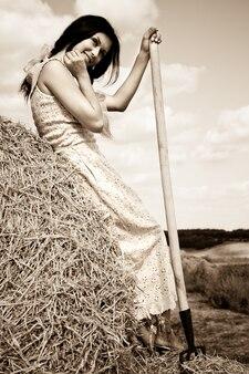 Jeune femme brune souriante en robe debout avec fourche à foin dans les mains dans le champ par une claire journée d'été. beauté dans le concept de campagne