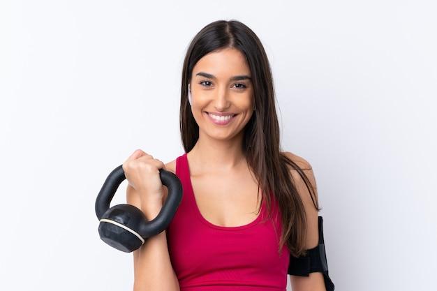 Jeune femme brune sport sur mur blanc isolé faisant de l'haltérophilie avec kettlebell