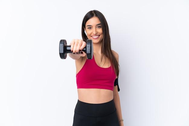 Jeune femme brune sport sur mur blanc isolé faisant de l'haltérophilie