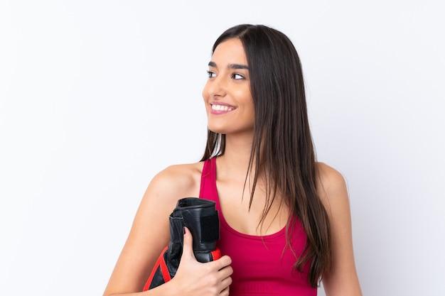 Jeune femme brune sport sur mur blanc isolé avec des gants de boxe