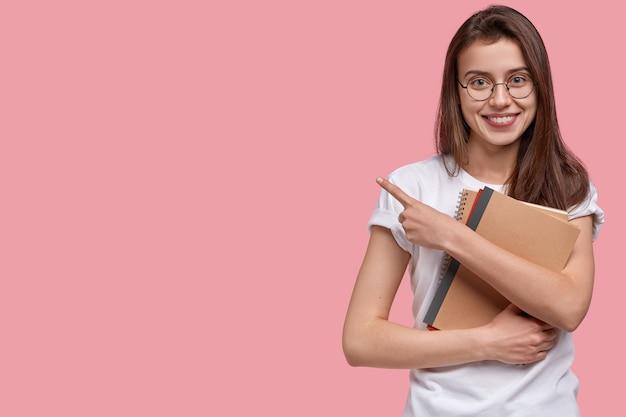 Jeune femme brune tenant des blocs-notes