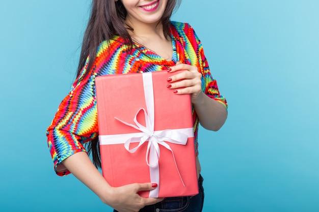 Jeune femme brune tenant une boîte-cadeau rouge dans ses mains