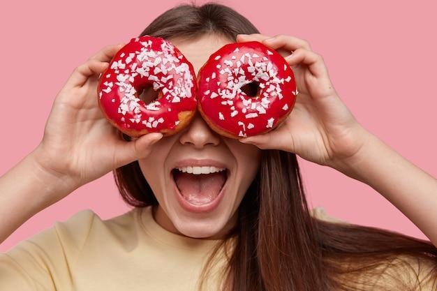 Jeune femme brune tenant de délicieux beignets
