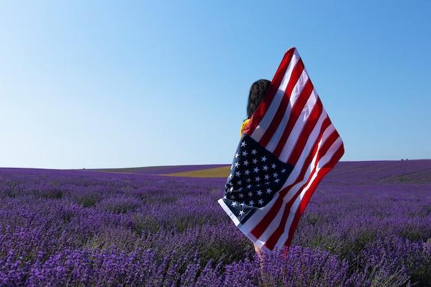 Une jeune femme brune tenant le drapeau des états-unis d'amérique contre le ciel ensoleillé. memorial day et concept de jour de l'indépendance des états-unis.