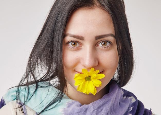 Jeune femme brune tenant une fleur jaune dans sa bouche