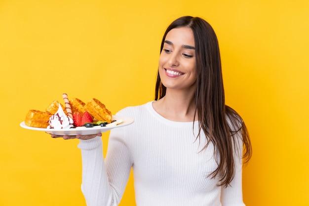 Jeune femme brune tenant des gaufres sur un mur isolé avec une expression heureuse