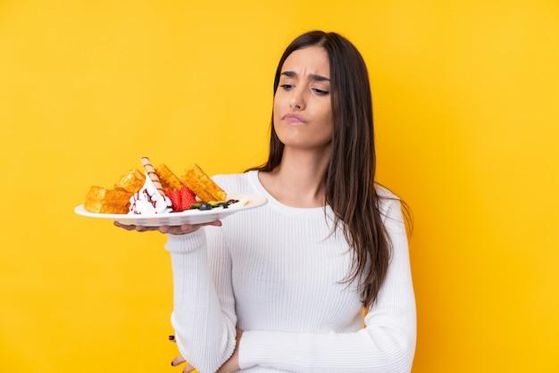 Jeune femme brune tenant des gaufres sur un mur isolé avec une expression triste
