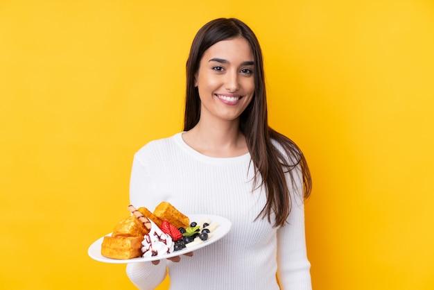 Jeune femme brune tenant des gaufres sur un mur isolé, souriant beaucoup