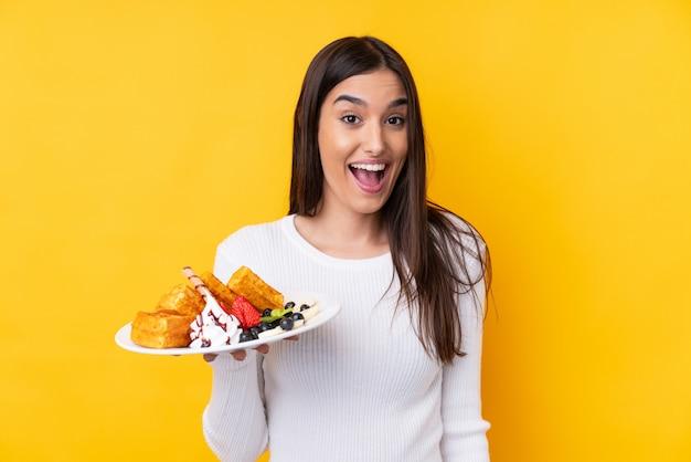 Jeune femme brune tenant des gaufres sur un mur isolé avec surprise et expression faciale choquée