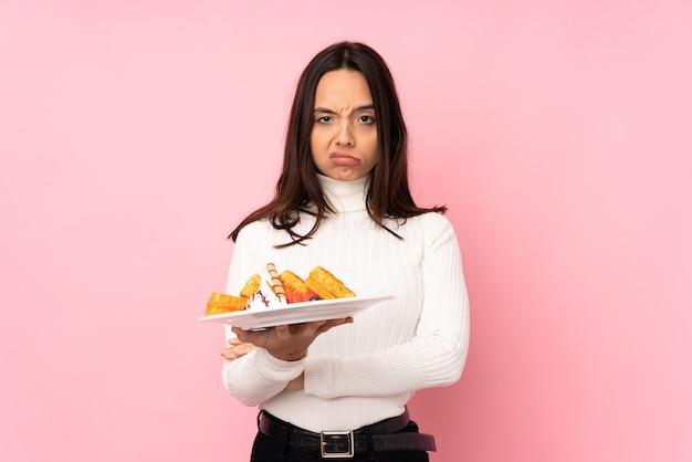 Jeune femme brune tenant des gaufres sur un mur rose isolé se sentir bouleversé