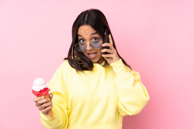 Jeune femme brune tenant une glace cornet isolée