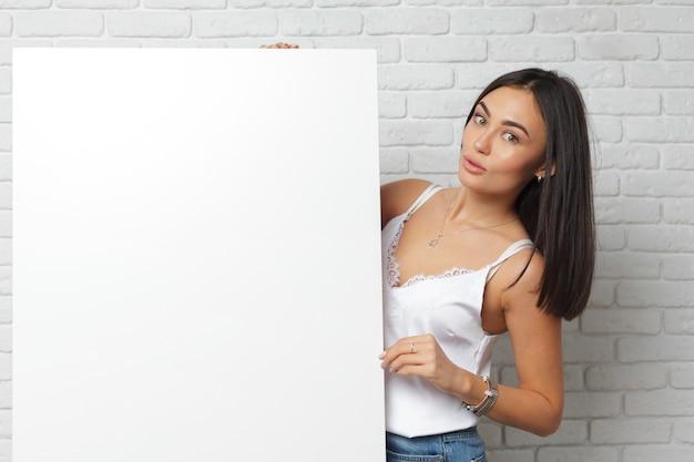 Jeune femme brune tenant un grand tableau blanc vierge avec espace de copie