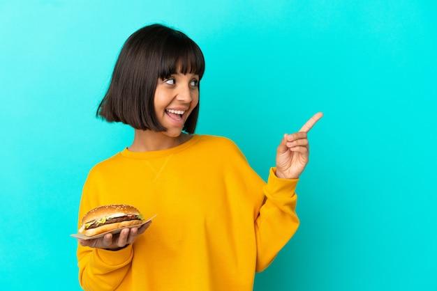 Jeune femme brune tenant un hamburger sur fond isolé dans l'intention de réaliser la solution tout en levant un doigt vers le haut