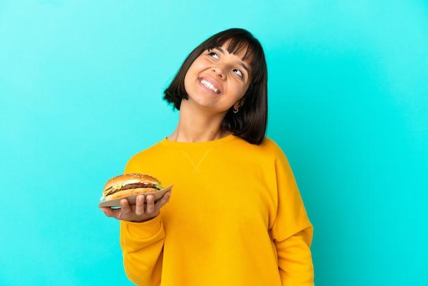 Jeune femme brune tenant un hamburger sur fond isolé en riant