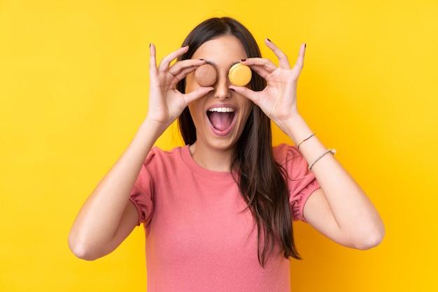 Jeune femme brune tenant des macarons français colorés avec une expression surprise