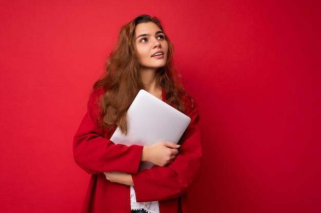Jeune femme brune tenant un ordinateur portable proche ayant une idée portant un cardigan rouge et un chemisier blanc regardant la caméra isolée sur fond rouge.