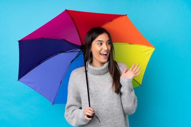 Jeune femme brune tenant un parapluie sur le mur bleu avec une expression faciale surprise