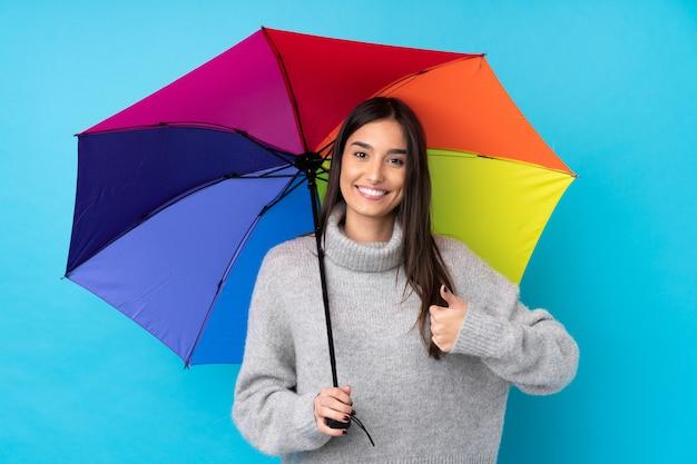 Jeune femme brune tenant un parapluie sur le mur bleu isolé donnant un coup de pouce geste