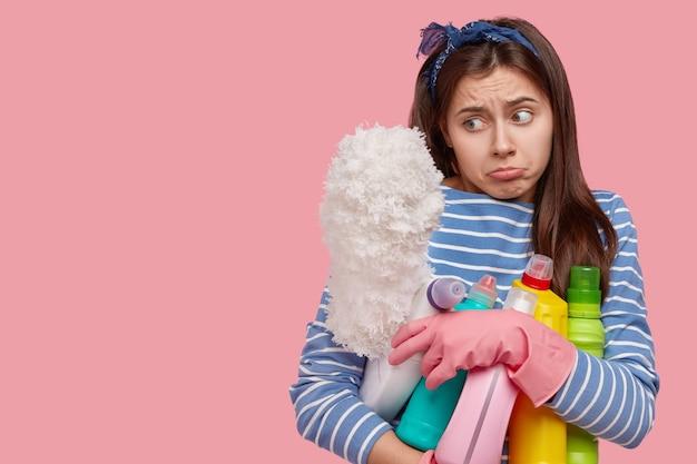 Jeune femme brune tenant des produits de nettoyage
