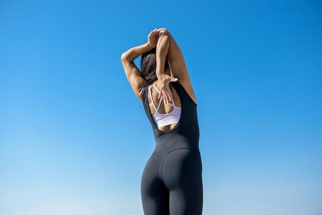 Jeune femme brune en tenue de sport faisant étirement ses jambes après l'entraînement sur le lac près de la journée. mode de vie sain