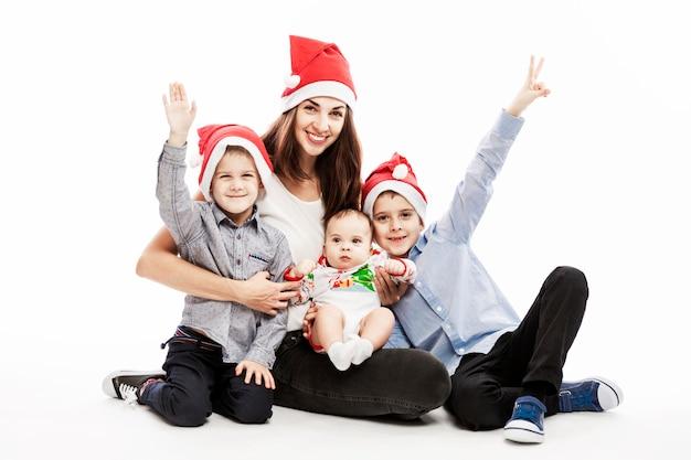 Jeune femme brune avec trois enfants en chapeaux santa souriant et étreignant. l'amour et la tendresse. ambiance festive.