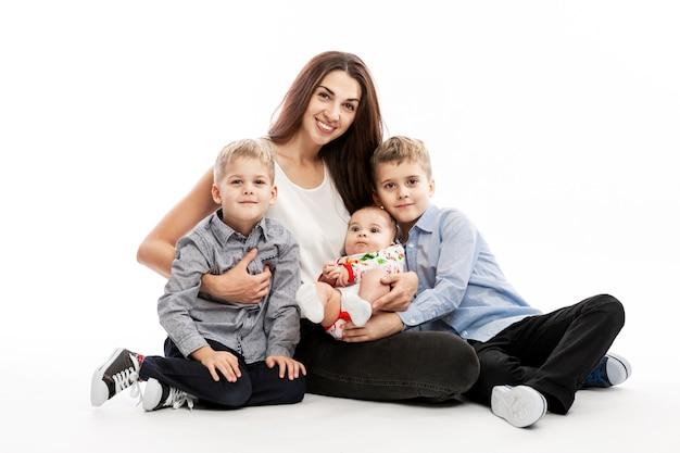 Jeune femme brune avec trois enfants souriant et étreignant. l'amour et la tendresse.