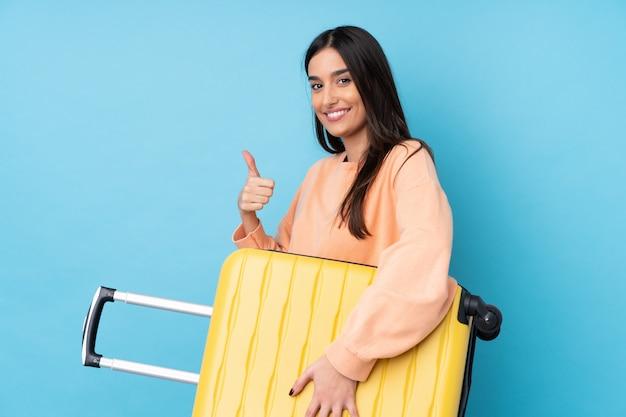 Jeune femme brune en vacances avec valise de voyage et avec le pouce vers le haut
