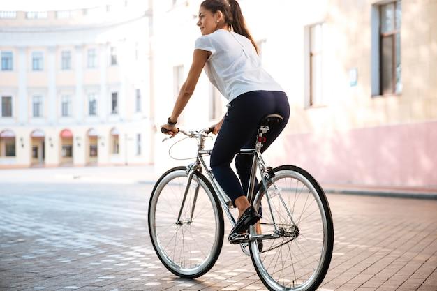 Jeune femme brune à vélo dans la rue de la ville