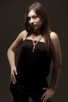 Jeune femme brune en vêtements décontractés noirs et accessoires massifs debout sur fond gris en studio photo
