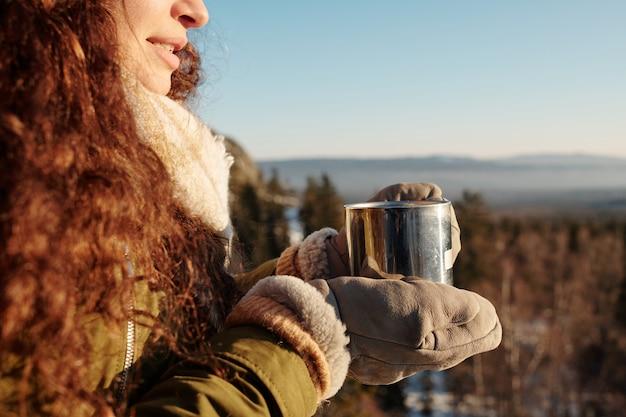 Jeune femme brune en vêtements d'hiver tenant la tasse