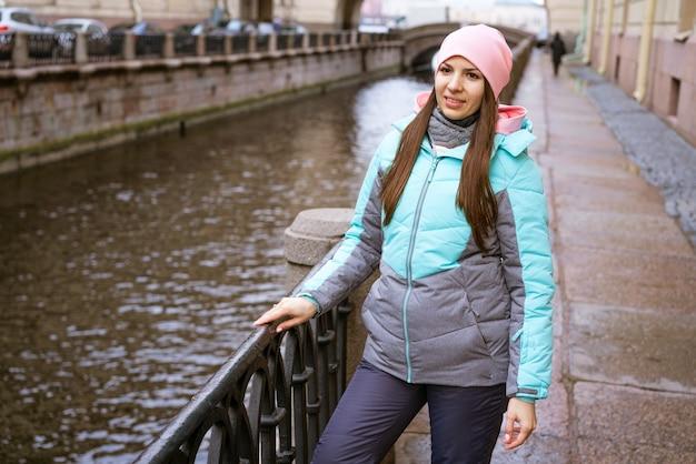Jeune femme brune vêtue de vêtements chauds et d'un chapeau rose se tient près de la rivière et sourit à l'extérieur aux couleurs vives...