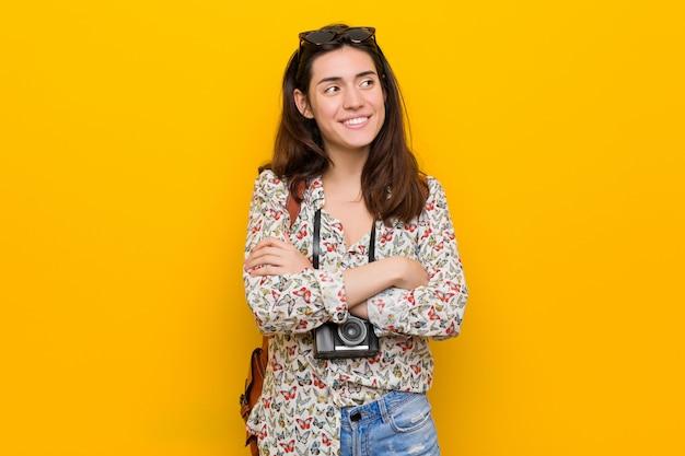 Jeune femme brune voyageur souriant confiant avec les bras croisés.