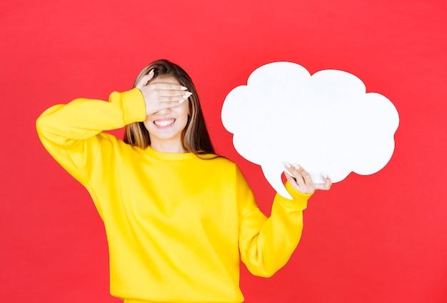 Jeune femme avec une bulle de dialogue fermant les yeux avec la main sur le rouge