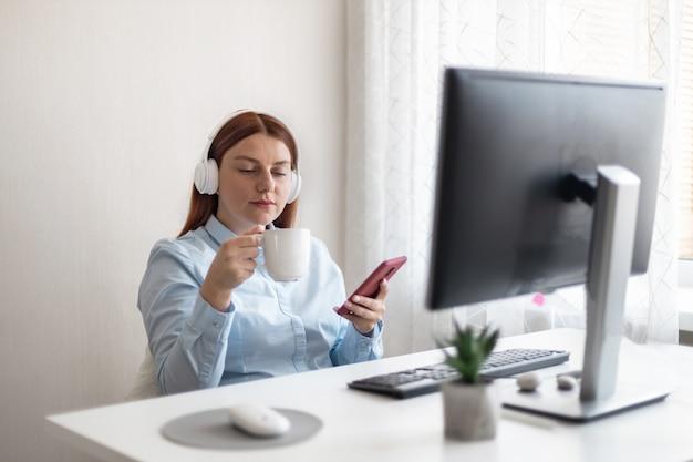 Jeune femme de bureau caucasienne assise dans des écouteurs sans fil avec une tasse de café ou de thé chaud sur le lieu de travail à la maison ou au bureau