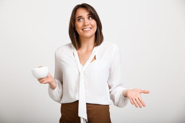 Jeune femme de bureau heureux haussant les épaules, boire du café