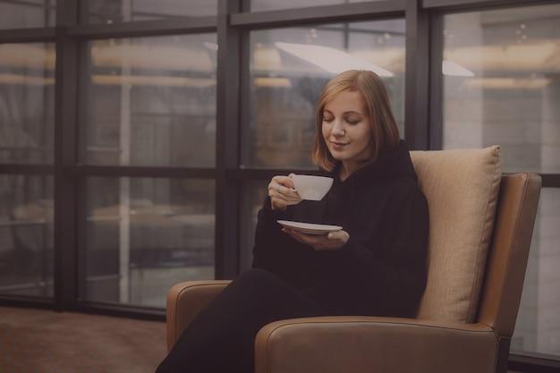 Jeune femme buvant du café assis sur une chaise
