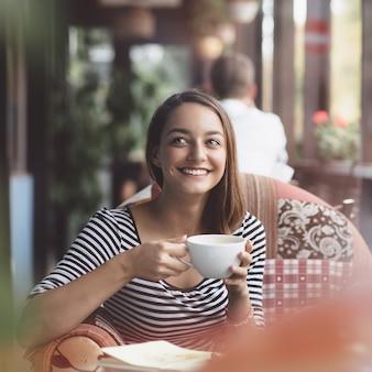 Jeune femme buvant du café au café urbain
