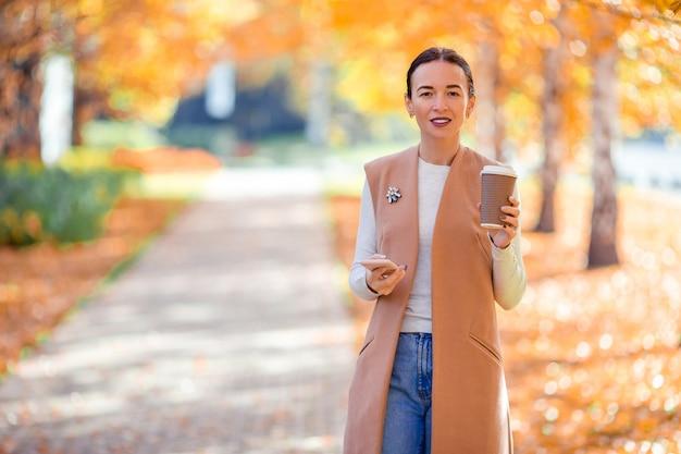 Jeune femme buvant du café en automne parc