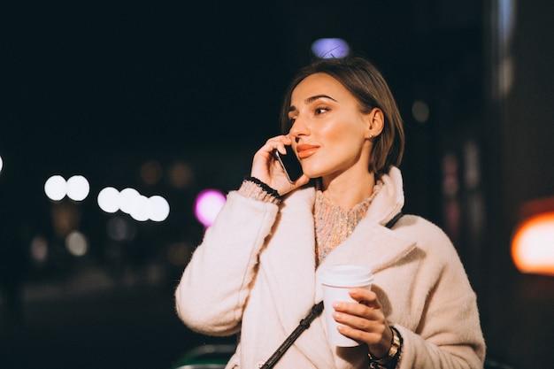Jeune femme buvant du café dans la rue de nuit