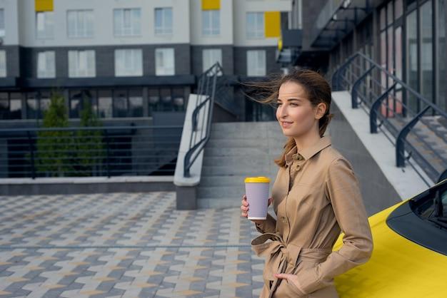 Jeune femme buvant du café dans la rue