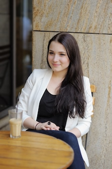 Jeune femme buvant du café glacé et dans un café en plein air